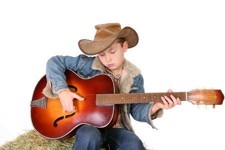 stockman: A boy strums a tune on an acoustic guitar