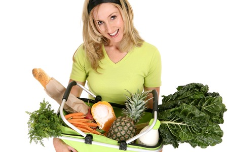 A woman with a shopping basket filled with food essentials,  fresh fruit, vegetables, milk and bread. Stock Photo