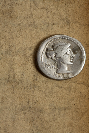coinage: Silver AR denarius from Roman Republic dated 89bc on aged paper.  Front side depicting female draped hair taken in chignon.  Behind the nape of the neck, ROMA, Under the neck, M.Cato. Issuance of coinage was administered by annuallly elected magistrates ( Stock Photo