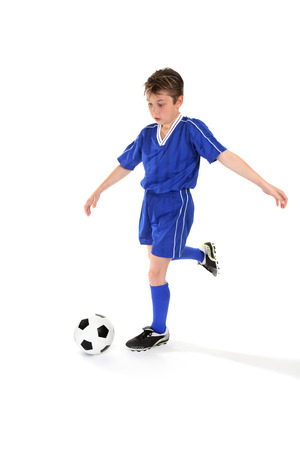 A boy kicks a soccer ball. Some slight motion