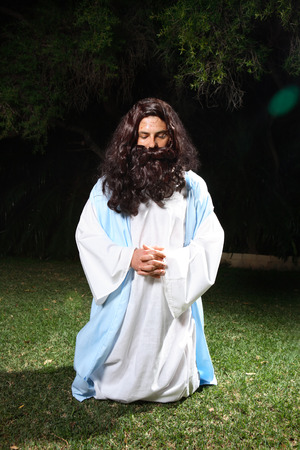 Jesus on knees praying earnestly in the Garden of Gethsemane. photo