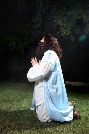 Side view of Jesus in Garden of Gethsemane on knees praying to God.   photo