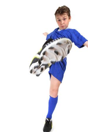 A boy kicks high.  Kicking leg in motion.