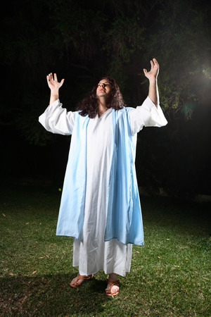 jesus standing: Biblical man wearing white robe and over cloak bathed in light praising and glorifying God.   From (Psalm. 29:2) Give unto the Lord the glory due unto his name; worship the Lord in the beauty of holiness