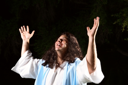 worshipping: A man dressed in robe hands raised in the air praising or worshipping God