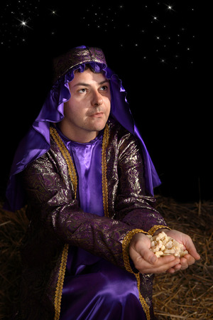 Wise man arrayed in majestic purple robe woven with gold metallic thread is offering in his palms finest pure frankincense. Focus to face. Stock Photo