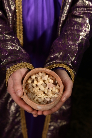 wisemen: Wise man arrayed in purple cloak embrodered with metallic gold thread, his hands holding an ancient clay pot filled with the best hojari frankincense resin tears from dhofar region of Oman.  The aroma is warm and citrusy