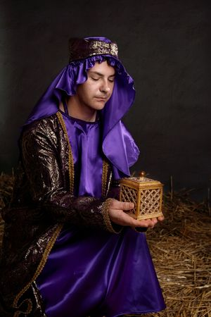 immanuel: Focus to gift.  Wise man kneeling on straw in a stable, bringing a gift for the  Jesus. Stock Photo