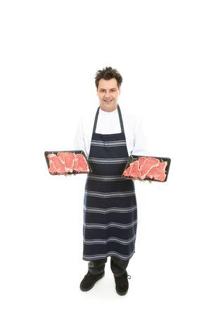 Friendly butcher holding trays of tender steak.