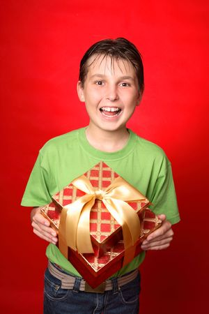 jovial: Jovial child holding a red and gold gift tied with gold ribbon.