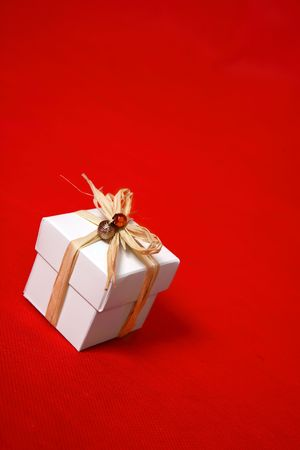occasions: A white gift box tied with raffia and decorated with beads sits on a red background.  Suitable for birthday, Christmas, valentine,  or other special occasions. Stock Photo