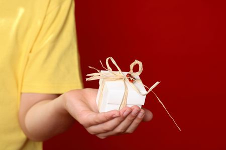 bonbonniere: Hand offering a small decorated  gift against a dark red background, eg Christmas, birthday, mothers day special occasion.