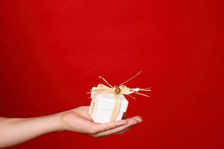 compassionate: Child handing a small gift tied with raffia in palm of hand - red background - space for copy