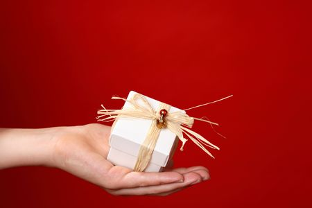 Handing a small gift tied with raffia and decorated with red and gold beads against a red background - suitable for Christmas, valentine or other special occasion.