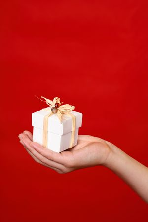 bonbonniere: A wrapped and decorated giftbox in the palm of a hand against a red backdrop - suitable for Christmas, birthday or other special occasion Stock Photo