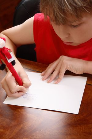 A child writing a letter to santa.  Focus to hands photo