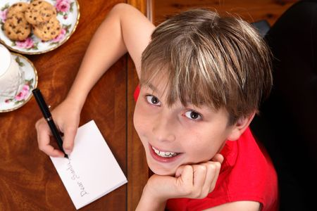 A child sitting at a desk writing a letter for Santa or Christmas card. photo