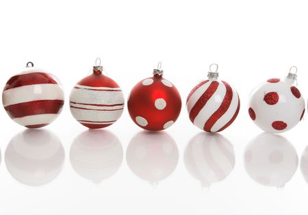 Red and white Christmas baubles with various designs on a white background. photo