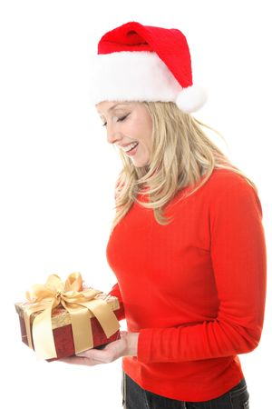 A smiling woman receiving a Christmas gift.   She is looking down and smiling in appreciation. photo
