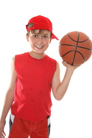 Hot, smiling child holding a basketball in one hand after the game photo