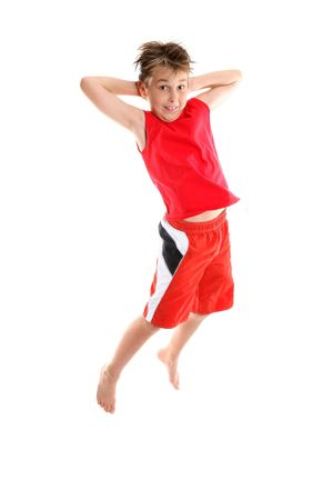 A boy jumping into air hands behind his head photo