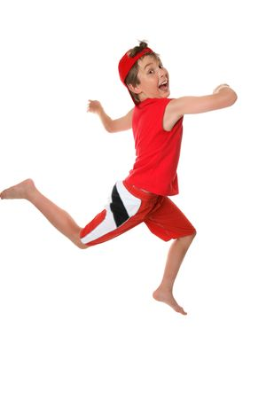 Happy healthy boy leaping or running and looking over shoulder and having fun Stock Photo