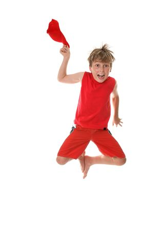 A boy with zestful energy jumps high off the floor and takes off his hat. photo