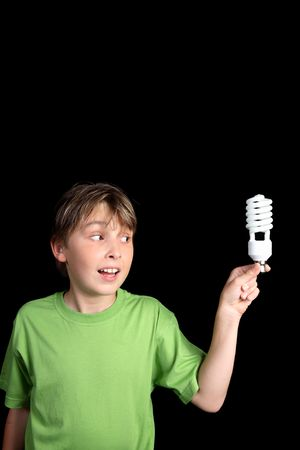 A boy holds an energy efficient compact fluorescent light bulb with space for your text or message. vertical. Stock Photo - 2367061
