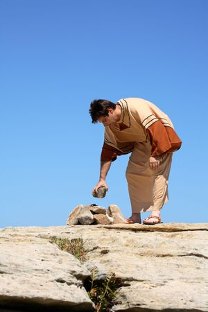 capital punishment: Full length man in brown and beige  tunic robe bending over near a pile of rocks.  Concept sin, law or culture.  This form of punishment was used in many ancient cultures and is still used in some cultures today.   Space for a heading, title or verse. Stock Photo