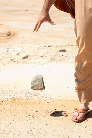 Symbolic concept of man dropping a stone from his hand.   Concept, peace, mercy, pardon, forgiveness, compassion.