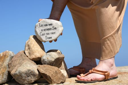 forgiven: A man holds a white rock inscribed with a bible verse from John 8:7 - Let him who is without sin cast the first stone.    Closeup.  Focus to rock. Stock Photo