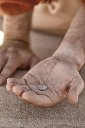 Hand holding a single coin - beggar, destitute, donation, charity, good samaritan, etc,  Closeup with shallow dof.