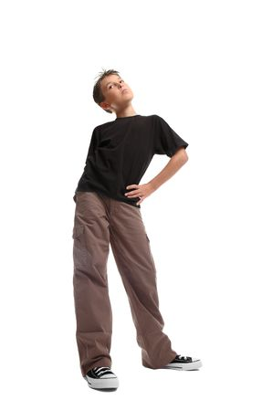 looking sideways: Standing boy ina plain  black t-shirt and cargos.  He is looking sideways. viewpoint from ground level.