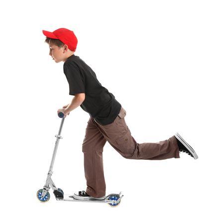 ni�o empujando: Boy inclinado hacia delante y empujando la silla de ruedas motorizada con un pie para recoger la velocidad - en un fondo blanco.