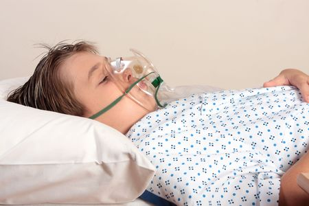 A child resting on a bed wearing patient gown has an oxygen mask or inhaler over face. photo