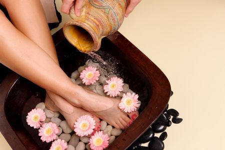 soothing: A woman enjoys a soothing foot spa pedispa Stock Photo