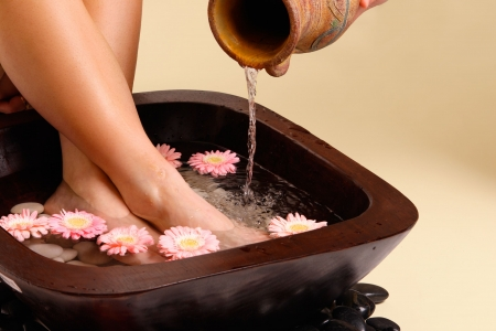 pedicure: Water pouring from an earthenware pot into a luxurious aromatic foot soak