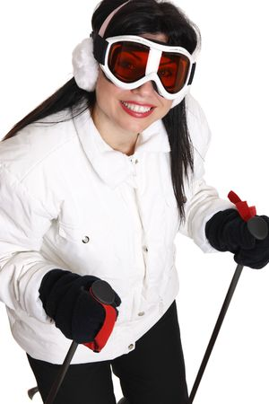 black ski pants: Female skier in white parka, black ski pants wearing ear muffs and ski goggles