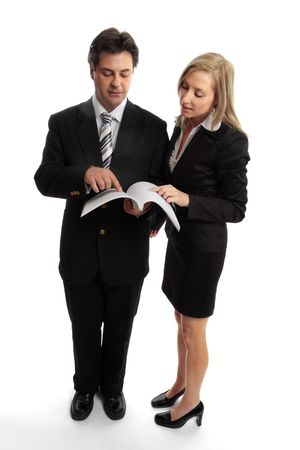 discutere: Due dirigenti aziendali lettura una relazione, di un contratto, gara d'appalto o un altro documento.  Archivio Fotografico