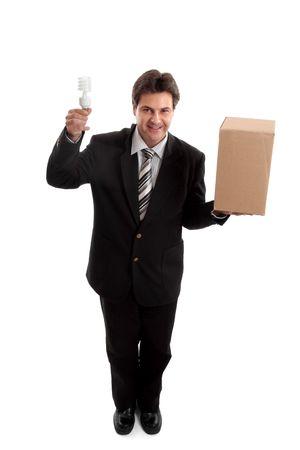 unconventional: Pensi fuori della scatola... Un uomo di affari che equilibra una scatola in una mano e tenuta una lampadina efficiente di energia nellaltra. per esempio le idee, pensare laterale, la prospettiva differente, non convenzionale, lenergia di eco, linnovazione, ambiente hanno collegato le edizioni o la c