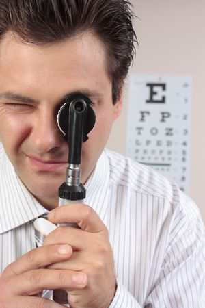 ophthalmic: Eye doctor looking through an opthalmoscope.
