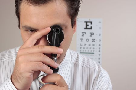 ophthalmic: An optometrist turning the lens dial of the opthalmoscope while examining a patients eyes. Stock Photo