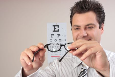 An optometrist examining a pair of eyeglasses frames. photo