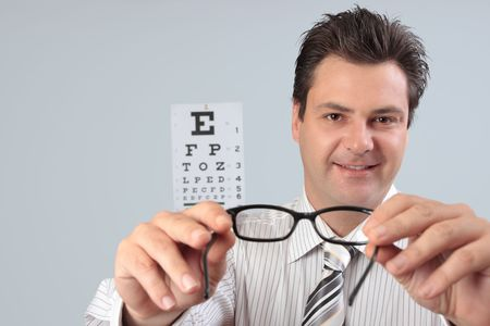 An optometrist putting eyeglasses spectacles  on a customer patient.
