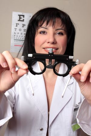 ophthalmic: Optometrist or eye doctor about to put trial frames on a patient during a vision checkup.