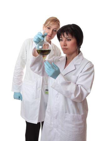 Two female scientists analyse chemical mixture. photo