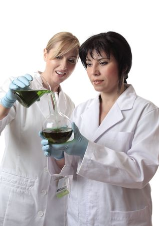 People, pouring liquid from a beaker into a round flat bottom flask. photo