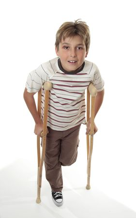 An injured child with sprained ankle using crutches. photo