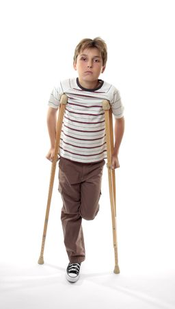 disability insurance: Sad melancholy boy with sore ankle using crutches