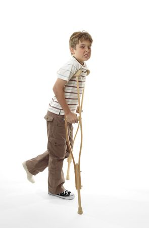 wincing: An injured boy with sore ankle using crutches